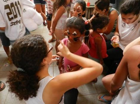 Isis Rangel, estudante de Jornalismo, pintando os rostos das crianças no Projeto Formiguinha. (Créditos: Isis Rangel)