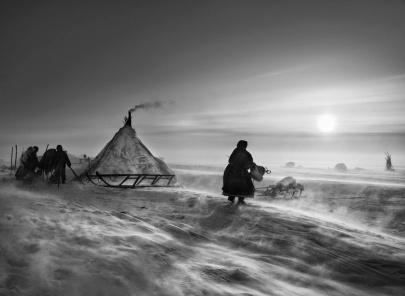 Os Nenets, povos do norte da Rússia, em meio a baixas temperaturas,  fazem reparações nos trenós e nas peles de renas para se manterem ocupados. 2011. (Foto: Sebastião Salgado/Exposição Gênesis)