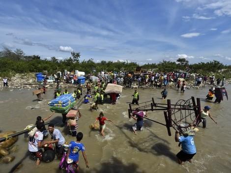 Colombianos deportados e famílias com receio de expulsão cruzam o rio Tachira na volta à Colômbia. (Créditos: AFP Photo/Luis Acosta)